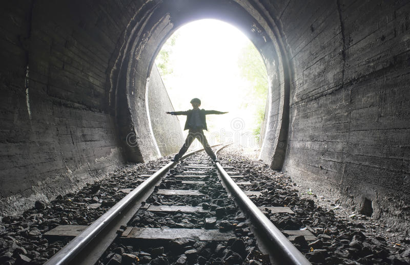Child walking in railway tunnel. Vintage clothes stock photo