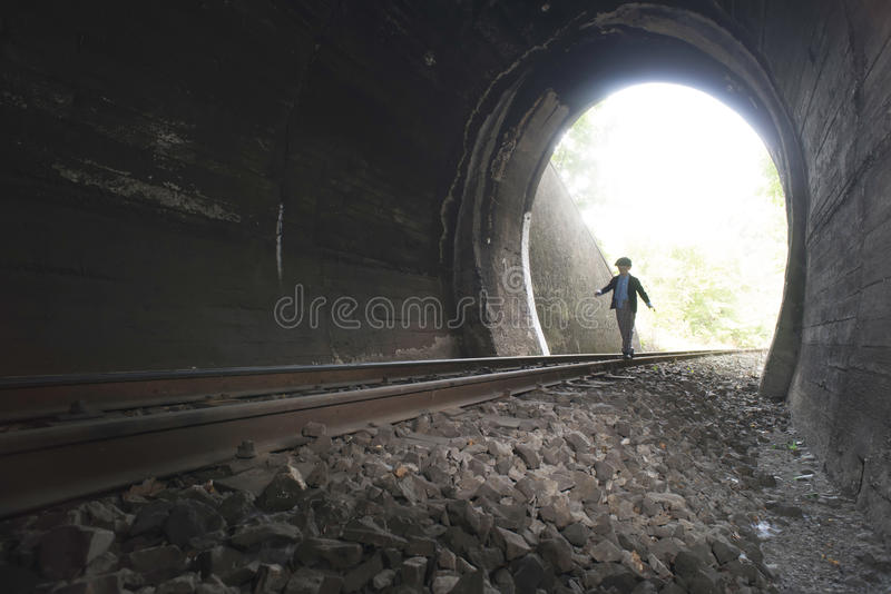 Child walking in railway tunnel. Vintage clothes stock image