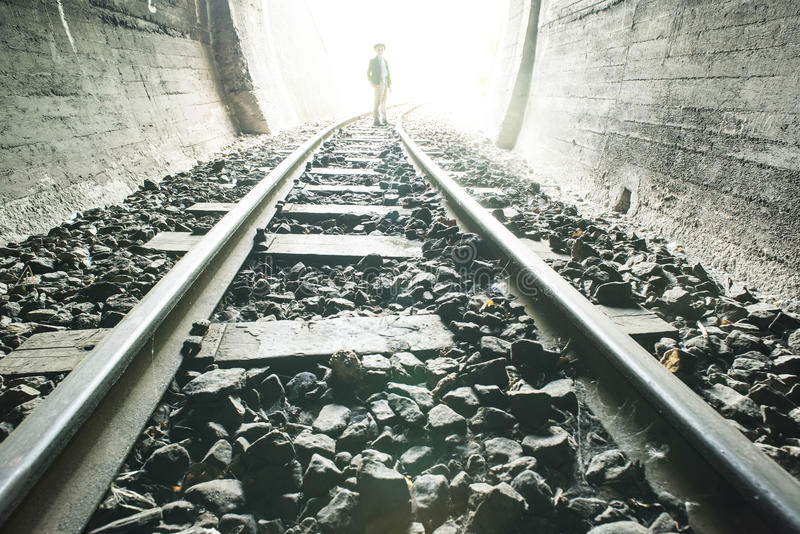 Child walking in railway tunnel. Vintage clothes royalty free stock photo