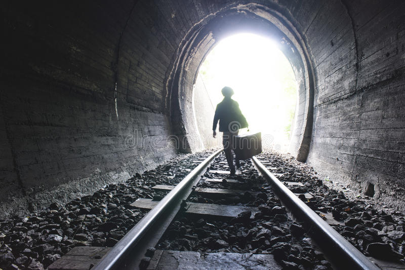 Child walking in railway tunnel. Vintage clothes royalty free stock photos