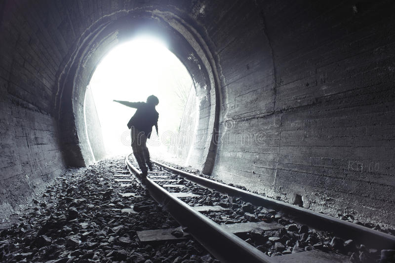 Child walking in railway tunnel. Vintage clothes stock images