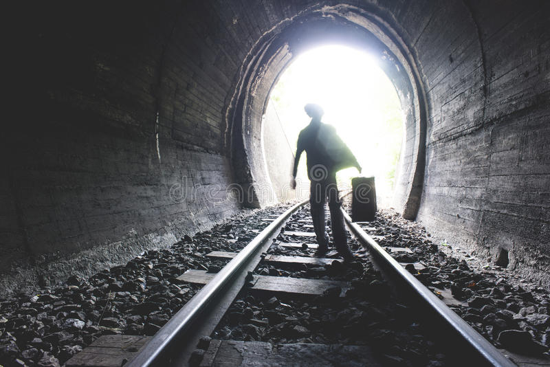 Child walking in railway tunnel. Vintage clothes royalty free stock image