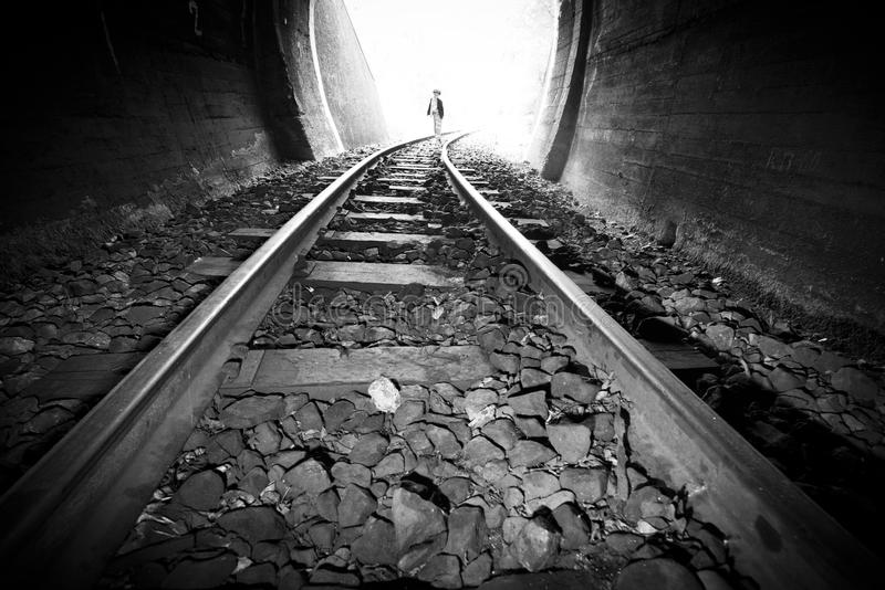 Child walking in railway tunnel. Vintage clothes stock photography