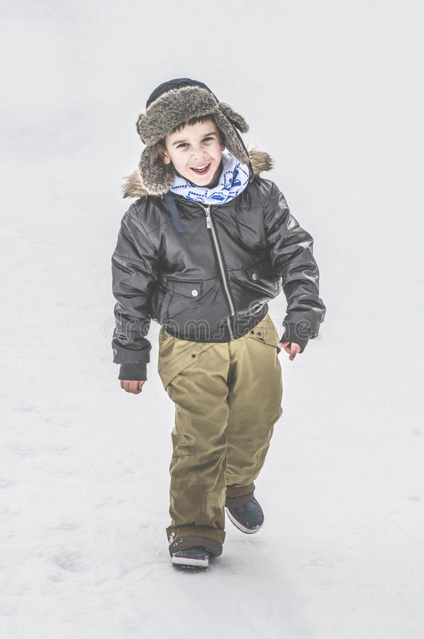 Child walking on the snow stock image
