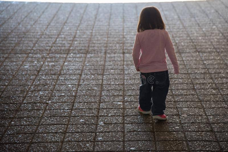 Child walking to the light stock photography