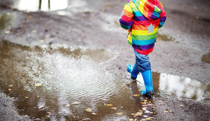 Child walking in wellies in puddle on rainy weather royalty free stock images