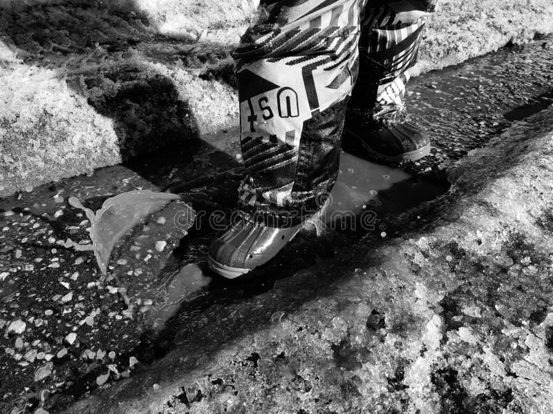 A child walks in boots through puddles in spring or winter in sunny weather. stock photography