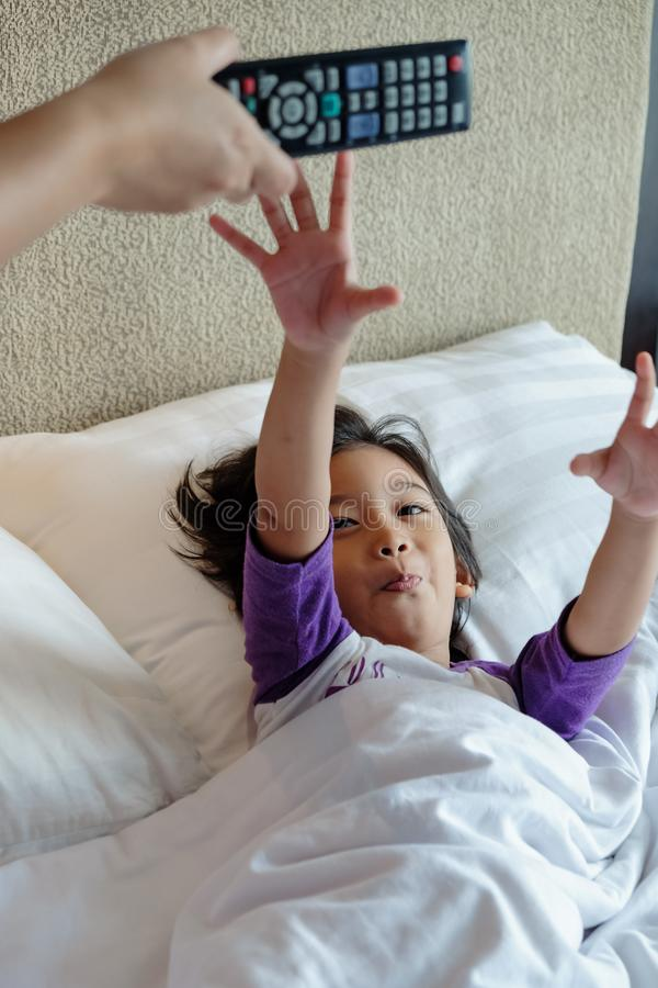 Asian Child On Bed Wants to Take Over Television Remote Control from His Parent Hands. Addiction or Parental Advisory Concept stock images