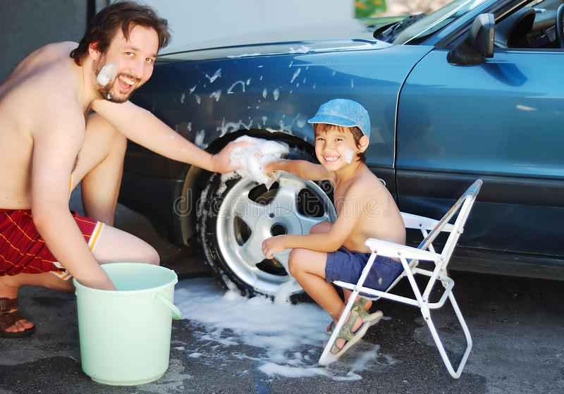 Child washing car and toy car with his father stock photo