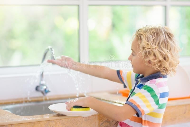 Child washing dishes. Home chores. Kid in white kitchen cleaning plates after lunch at window royalty free stock photos