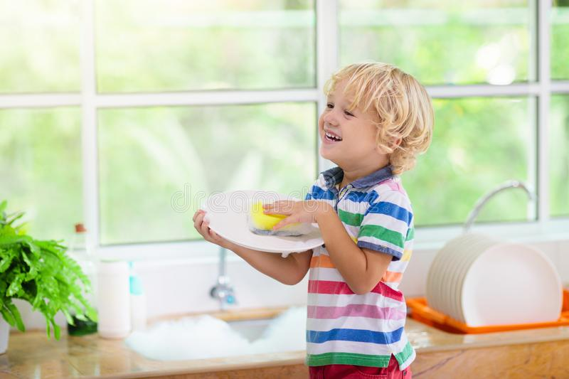 Child washing dishes. Home chores. Kid in white kitchen cleaning plates after lunch at window stock image