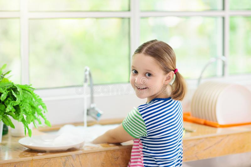 Child washing dishes. Home chores. Kid in white kitchen cleaning plates after lunch at window royalty free stock photography