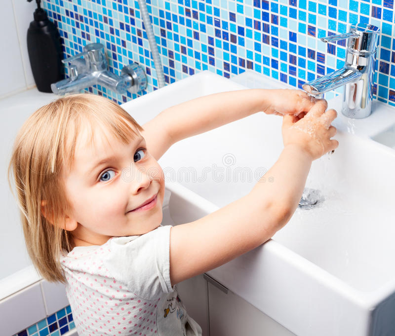 Child washing hands. Little girl washing her hands in bathroom sink stock images