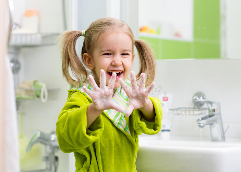 Child washing hands. And showing soapy palms stock image