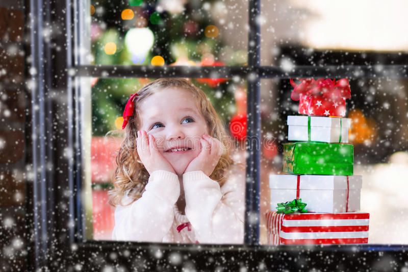 Child watching out of window on Christmas eve royalty free stock photo