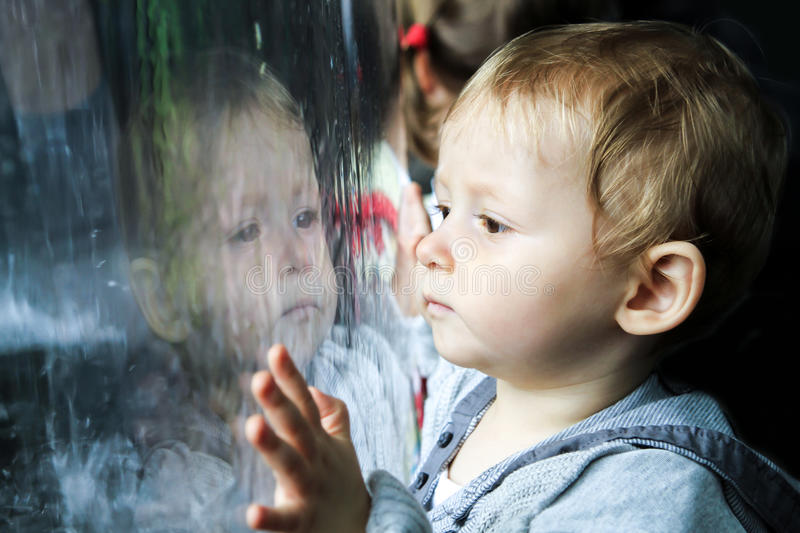 Child watching the rain on window stock photos