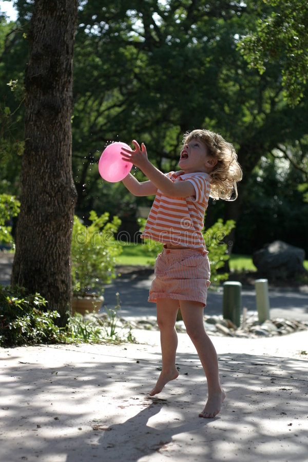 Child and Water Balloon. Throwing a water balloon up in the air freezing the motion stock photography