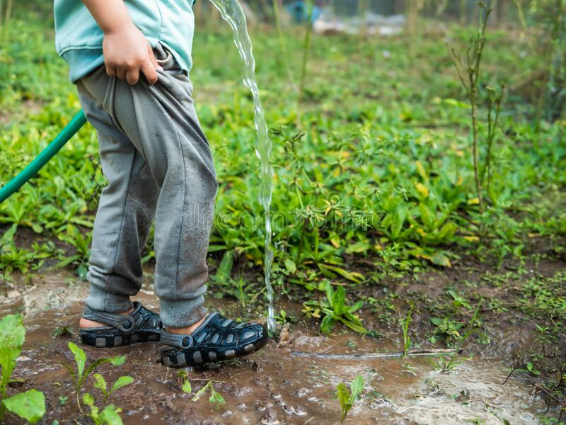 Child with water hose to watering plant to garden, legs and shoe with dirty mud. Happy relaxing activity in summer stock photography
