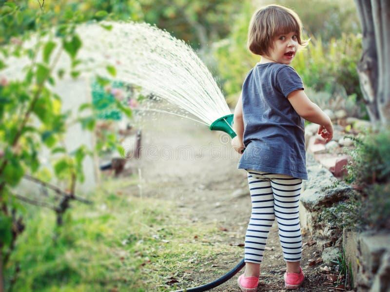 Child watering garden. Little happy girl watering garden stock images