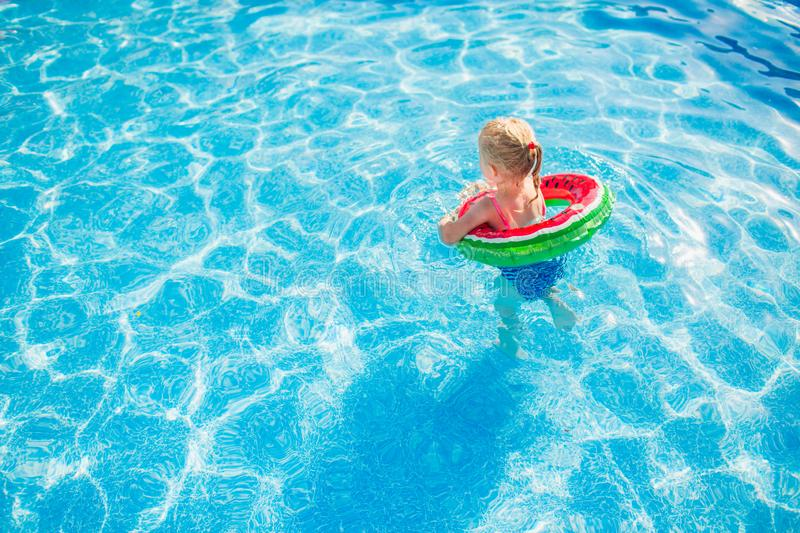 Child with watermelon inflatable ring in swimming pool. Little girl learning to swim in outdoor pool. Water toys and floats for stock photo