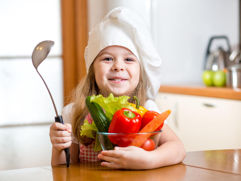 Child weared as cook with vegetables at kitchen royalty free stock photography