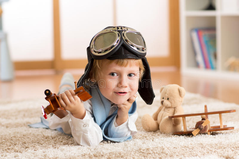 Child weared pilot or aviator plays with a toy airplane at home in nursery room. Concept of dreams and travels. Concept of dreams and travels. Child weared royalty free stock photos