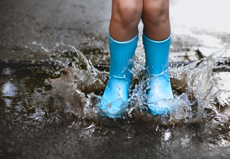 Child wearing blue rain boots jumping into a puddl. E. Close up stock photography
