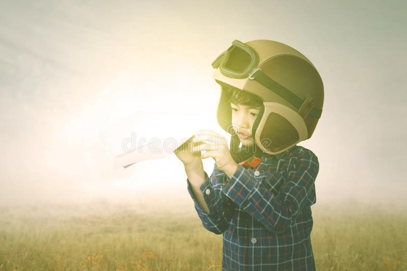 Child wearing helmet during plays a paper plane royalty free stock photography