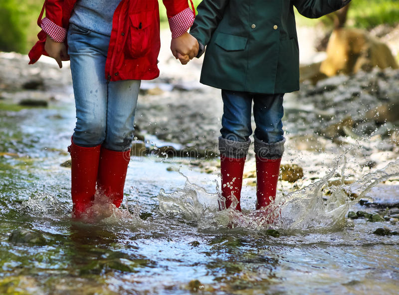 Child wearing rain boots jumping. Close up stock photography