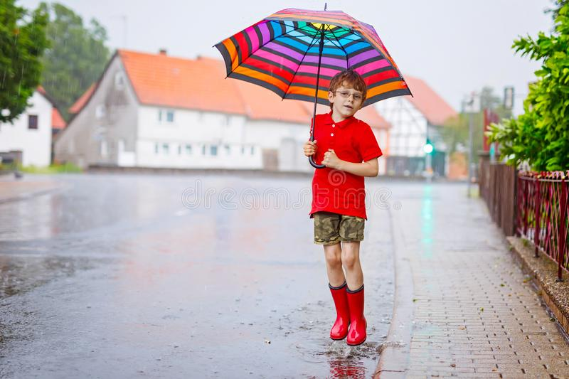 Child wearing red rain boots jumping into a puddle. Close up. Kid having fun with splashing with water. Warm heavy. Kid boy wearing red rain boots and walking stock images