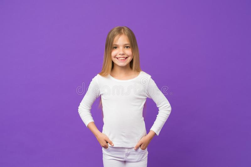 Child wearing white jumper and jeans, youth fashion concept. Girl with long shining blond hair. Lovely kid with big royalty free stock photo