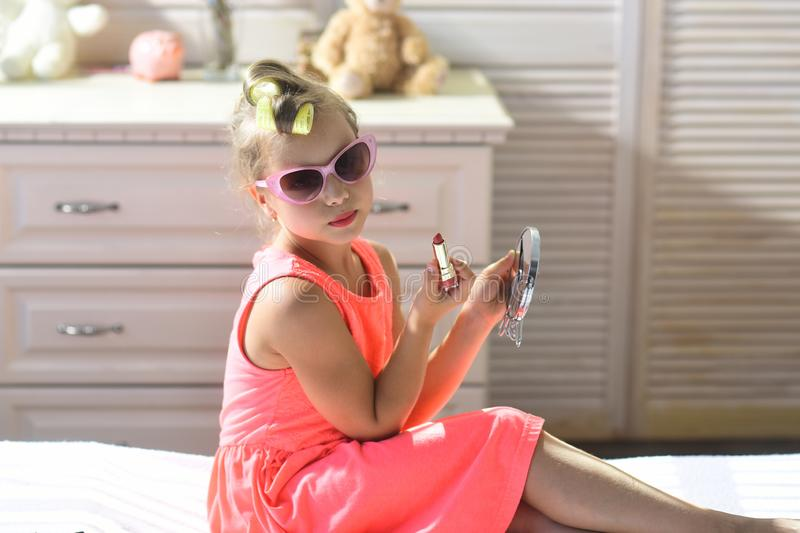 Child wears sunglasses and takes mothers cosmetics royalty free stock image