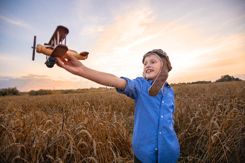 A child in a wheat field in the village with a retro plane in his hands. the boy dreams of becoming a pilot. evening beautiful sky royalty free stock photo