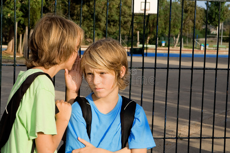 Child whispering at school stock photography
