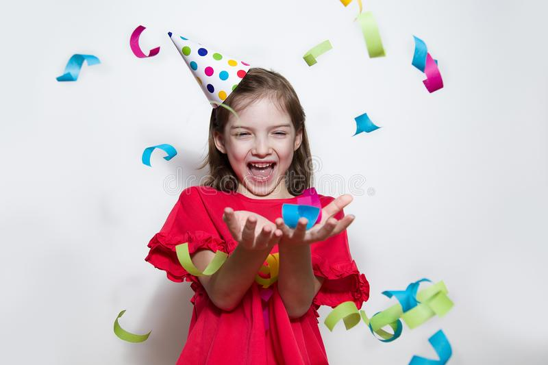 A child on a white background celebrates a bright event, wears a red dress and a cap. royalty free stock images