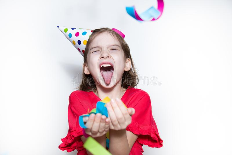 A child on a white background celebrates a bright event, wears a red dress and a cap. Birthday, New year`s carnival. A child on a white background celebrates a royalty free stock images