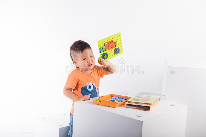 A child on a white background shows how he assembled a designer machine stock image