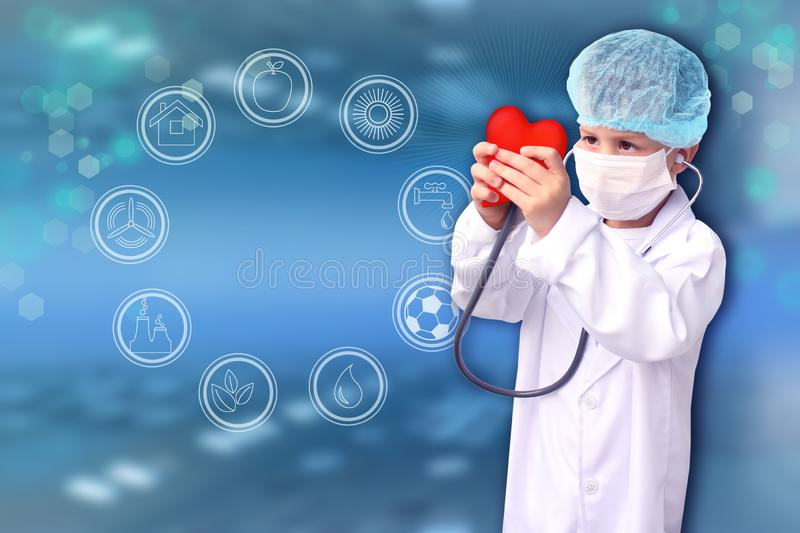 Child in a white doctor's coat, hat and mask attached a stethoscope to a red heart model, innovative research background, close- royalty free stock photo