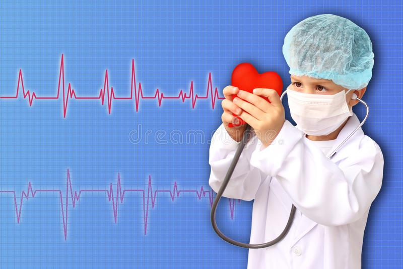 Child in a white doctor's coat, hat and mask attached a stethoscope to a red heart model, research background, close-up, face. Focus, medical, cardiology royalty free stock image