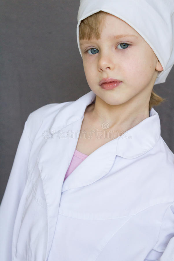 Child in a white medical robe. Child in a white medical white robe stock photo