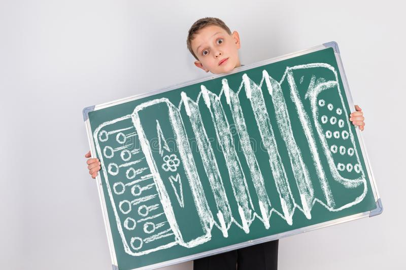 A child who loves to play on the nerves with his funny comic antics. The boy holds a small chalkboard with a drawing of accordion royalty free stock photo