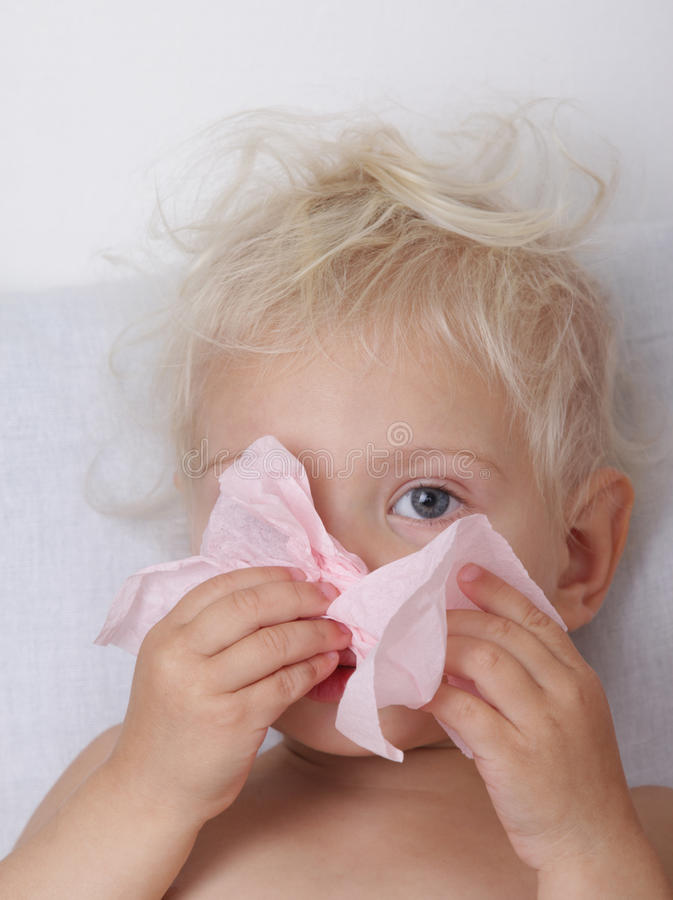 Child wiht runny nose. Little blond girl blowing her nose stock image