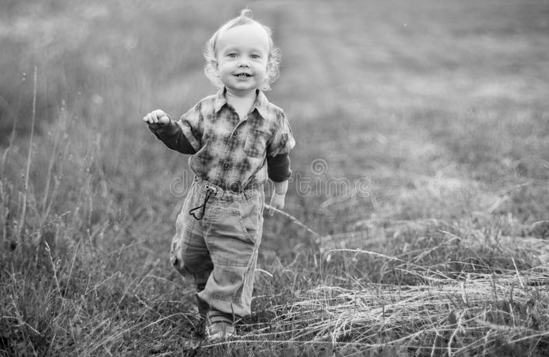 Child in wild field walking. With a smile, monochrome stock image