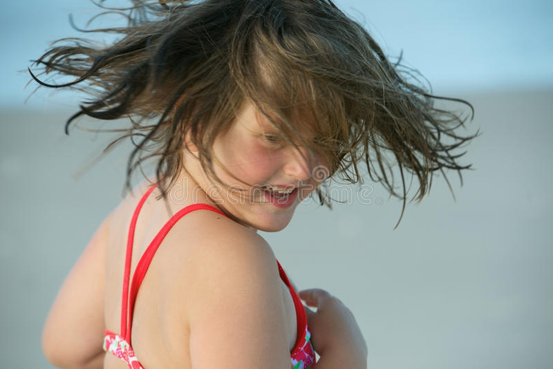 Child in the wind. Candid outdoors portrait of sweet little girl having fun with wind blowing in her hair at the beach