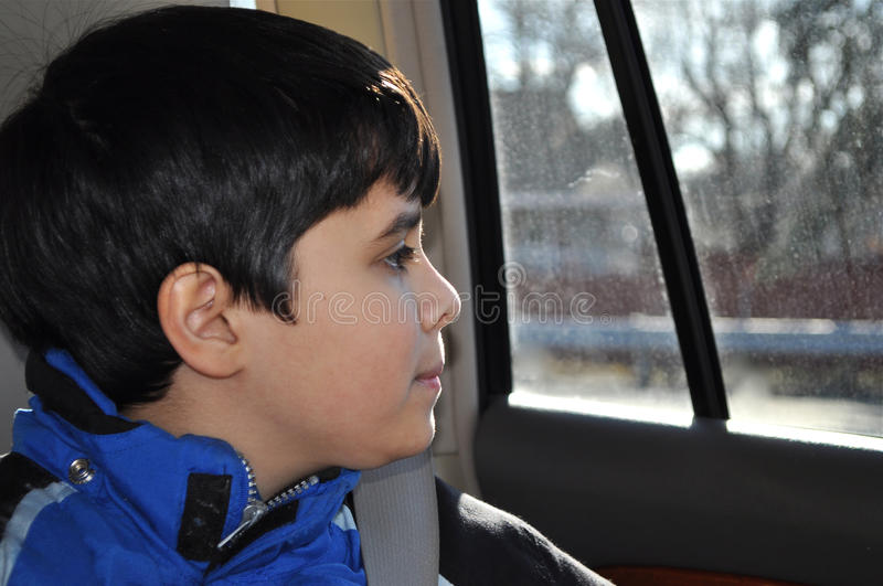 Child and Window. A young and cute boy is looking through the window royalty free stock photo