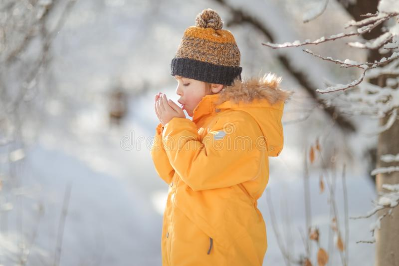 Child winter in in cold weather happy and runs around on snow drifts stock photos