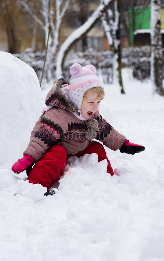 Child in winter. Girl rolling down the hills royalty free stock photo