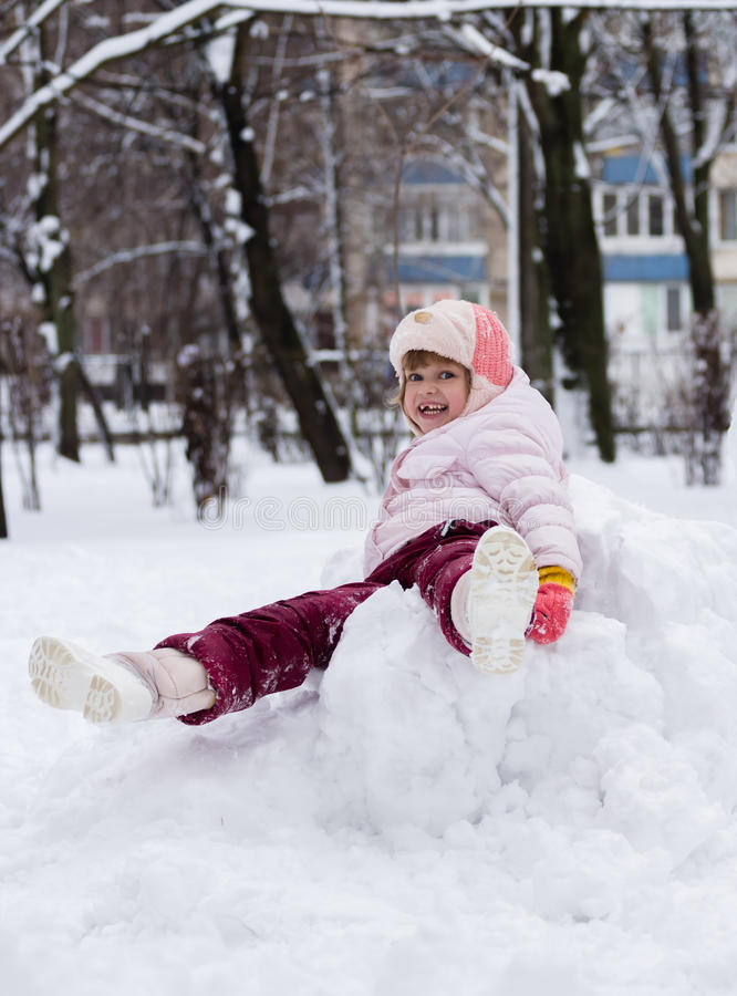 Child in winter. Girl rolling down the hills royalty free stock photos