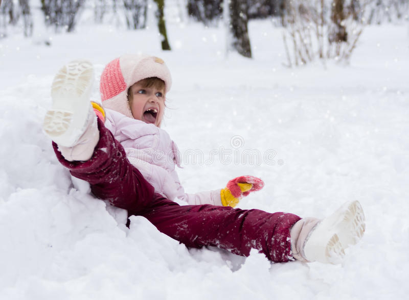 Child in winter. Girl rolling down the hills royalty free stock image
