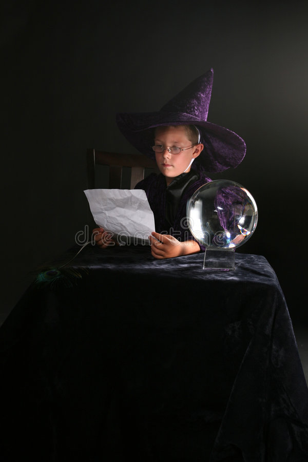 Child in wizard costume consulting his spell. Next to a crystal ball stock photo